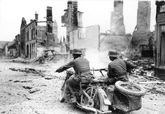 Nazi motorcyclists pass through a destroyed town in France in 1940. (Deutsches Bundesarchiv/German Federal Archive)