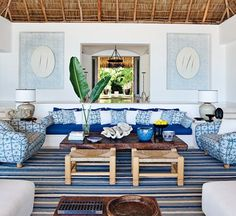 In a Mexican Martyn Lawrence Bullard designed home, the living room sofa, with seat and back cushions of Chameleon fabric by Perennials, is flanked by custom-made chairs upholstered in Kaba Ka...