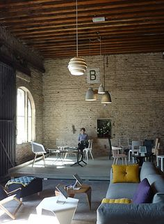 Loft ceiling & exposed brick & neutral palette with a pop of color & interesting pendant lighting fixtures