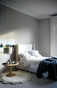 Grey and white bedroom with a cool round bedside table on a round rug