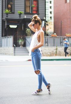 Loose Fitting White Tank Top with Slits on Sides, Bikini Top, Light Blue Jeans Ripped at the Knee, Plaid Slip-On Sneakers, Sunglasses and High Bun. #city #fashion