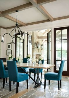 Dining Room decor ideas - Transitional style with aqua upholstered chairs, modern wood slab and metal table, rustic candelabra chandelier, boxed beam ceiling and slate tiled floor.