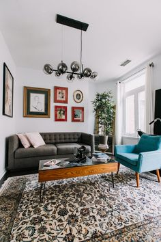 The coffee table is the Urban Outfitters Shadowbox Coffee Table. The oriental rug was purchased at a local auction. The sofa and light fixture are both from West Elm. The blue side chair is from Urban Outfitters.
