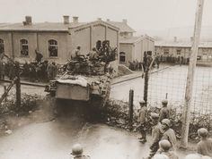 Allied POWS cheer as an American tank breaks through the barbed wire surrounding the POW camp in Hammelburg, Germany on April 8, 1945.    I am not sure if this was my father's prison or not, could be.
