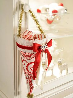 Adapt the Thanksgiving cornucopia for the Yuletide. This pretty paper cone is trimmed with stylish embellishments. Hang it from the tree as an ornament or a cabinet knob for decoration, or fill it with candy and give as a Christmas present to a coworker or friend