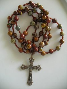 Handmade Catholic rosary 10mm red creek jasper highly polished natural stone translucent dark amber glass spacers 2 1/2 inch bronze crucifix Length 25 inches USPS First Class shipping weight 10 ounces Item #117CR
