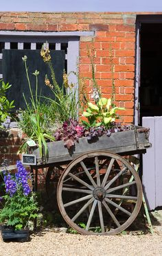 Farm cart antique wood with wagon wheels in front of rustic brick farm building barn trimmed in lavender color, with plants for sale Garden Wagon, Garden Cart, Garden Junk, Garden Sheds, Wagon Wheel Decor, Vintage Milk Can, Rustic Garden Decor, Old Wagons, Flower Cart