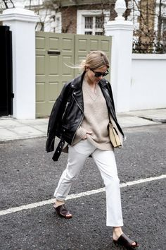 Rocking Autumn trends with a leather jacket and mules, with a beige jumper and white jeans.