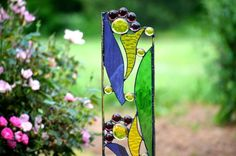 Every yard needs some garden art! This stained glass sculpture of purple and yellow abstract wildflowers will surely add color to your garden decor. Best of all, these flowers never need to be watered.  Do you have an area in your yard where you just cant get anything to grow? Perhaps you have greenery around your home and would like to sample some no bother, no fuss color. Plant these garden sculptures for constant color season after season.  Unique gift ideas for gardeners: Birthday…