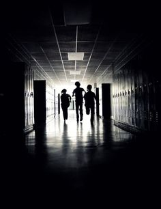 Their footsteps echoed through the barren hall lined with ancient metal lockers. The only light that there was was behind them. So why were they running towards the dark?
