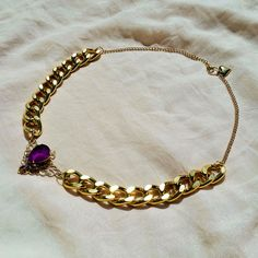 Chunky gold necklace with purple rhinestones set on a filigree pendant.