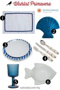 wishlist divino espaço com jogo americano de linho com fita azul, jogo de pratos com estampa azul, escultura de concha azul, talheres de cabo de osso, taça azul e prato em forma de peixe branco.