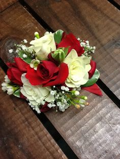 Small Red and White spray roses make this a stunning corsage, trimmed with baby's breath and some variegated Pitt finished off with a sheer red ribbon