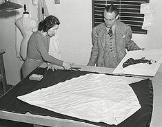 """Walter Plunkett en el taller de trabajo, con un boceto de uno de los diseños para """"Lo que el viento se llevó"""" (1939)"""
