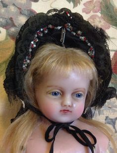 Twenty inch antique English poured wax girl modelling a lovely doll bonnet.