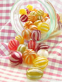 Photo of delicious fruit marbles hard boiled sweets in open jar with pink gingham check tablecloth.