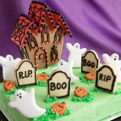 """Pre-Baked, Pre-Assembled Halloween Cookie House is one House with a Spirited View! The sheet cake """"cemetery"""" is inhabited by cookie ghosts that float among the cookie tombstones and pumpkin decorations."""