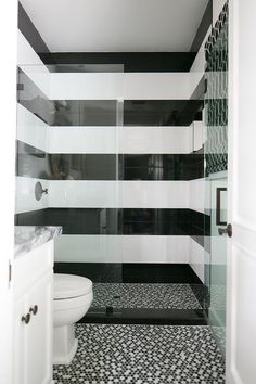 Black and white striped shower surround tiles are fitted with an oil rubbed bronze shower kit fixed behind a glass partition and beautifully complemented with black and white mosaic shower floor tiles which continue out into the bathroom to frame a white washstand.
