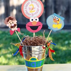 I like the tin pale with ribbons.@http://www.etsy.com/listing/60803162/elmo-birthday-party-centerpiece?ref=sr_gallery_38_search_submit=_search_query=elmo+party_noautofacet=1_page=9_search_type=handmade_facet=handmade%2Fpaper_goods