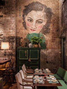 Painted portrait on exposed brick wall, antique Chinese cabinet Dining Room Design AtMr. Wongs