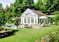 Traditional pool house with windows for lighting, white umbrellas and lounge chairs