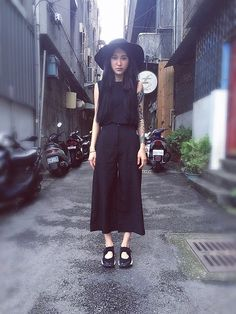 Mona Kuan, wearing a black sunhat, sleeveless top, and wide culottes with Air Rifts.