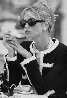 Chanel...love the suit ...I  am assuming that since she is holding a cigarette this was taken many years ago.