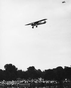 """Charles Lindbergh flying the """"Spirit of St. Louis"""" over the welcoming crowd in Forest Park, 19 June 1927."""