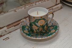 Candle in a demitasse with saucer