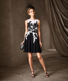 Short lace and guipure dress. Ever-popular black and white are combined exquisitely in this dress, creating a unique optical effect bursting with relief and texture, particularly visible over the bust. A delicate belt encircles the waist.