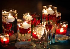 Floating candle centerpieces with red roses.