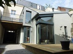 L'extension en ossature bois (Douglas) est recouverte d'un bardage en zinc et en lames de bois massif peintes. Elle se poursuit par une terrasse en pin traité, en limite de propriété, à moins de 3 mètres de la maison voisine.