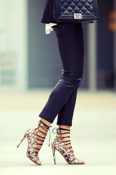 Nice outfit. Strappy high heels. Skinny black pants. Chanel purse.