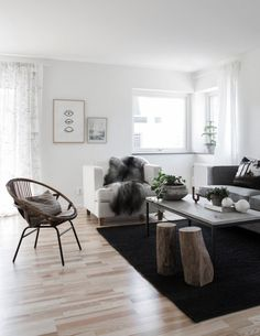 salon scandinave aménagé avec du parquet en bois clair, tabourets en bois brut, fauteuil blanc, canapé gris et couverture fausse fourrure