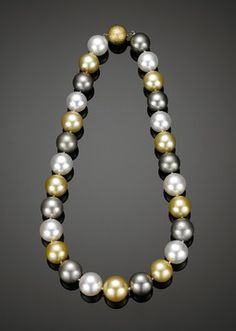 Outstanding in quality and design, this single strand of South Sea pearls presents the wide array of color in which these treasures are found. Exhibiting hues ranging from lustrous white and shades of gray to deep black and vibrant gold, these large pearls radiate from within and are among the rarest of all pearls. Ranging in size from 14.2mm to 16.4mm, these 27 luxurious gems from the sea are beautifully complemented by the 18K hammered yellow gold clasp.