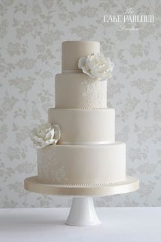 'REGENCY ROSE' Wedding Cake - Whimsical white sugar roses and simple lace piping decorate this pale coffee  coloured cake.