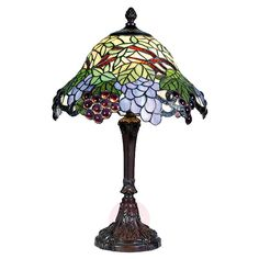 The table lamp Lotta impresses with its florally-inspired Tiffany design Glass elements in blue and green colours, which almost appear as authentic leaves and fruits, forming the colourful lampshade