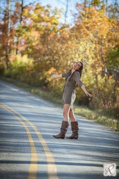 Fall senior portraits in the road with changing leaves, girl in cute dress dancing in the road