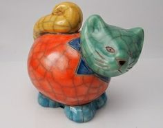 Raku Pottery Hand Painted & Glazed Cat. Each piece is handmade before being fired at a very high temperature. A Fair Trade card explaining the background of Raku Pottery comes with your piece.