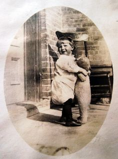 Antique photo:  Child hugging a teddy bear