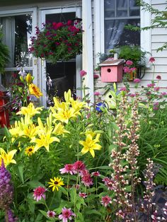 Beautiful cottage garden - love the bird houses and tall flowers!