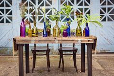 Pretty bottles in jewel tones dress up simple pieces of greenery.