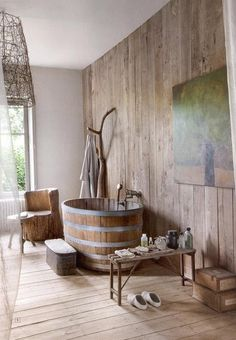 A wine barrel inspired tub and unfinished wood paneling give this bathroom a truly rustic feel.