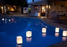 easy floating pool lanterns DIY by using Styrofoam squares, poking a dowel rod into each corner of the square, and then putting tissue or wax paper around the rodes