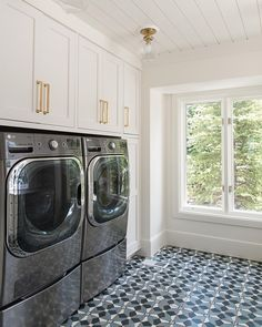 Patterned tile floor in laundry room with white cabinets and white shiplap ceiling.