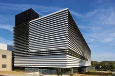 Edificio de Tecnología en Leuven: Un espacio para una nueva creación  Muros perimetrales se cierran con prefabricados de hormigón con aislamiento externo, los paneles de aislamiento térmico están acabados con revestimiento acrílico negro, delante de ellos una subestructura de aluminio soporta 600 milímetros de profundidad paletas de fibrocemento. La fachada secundaria sirve como una capa adicional de protección térmica y un escudo de agua de lluvia...