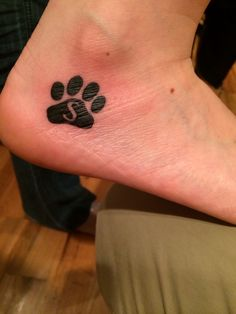 Paw print tattoo with my buddies initial inside. Love my pooch. ❤️