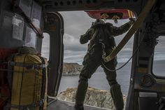 Flight engineer Master Corporal William Kerby, from 103 Search and Rescue Squadron at 9 Wing Gander, Newfoundland and Labrador, positions himself in the rescue door of a CH-149 Cormorant helicopter to assess the rocky shore below before conducting search and rescue training near Twillingate, in Newfoundland on May 11, 2016.. PHOTO: Corporal Anthony Laviolette, SW2016-0099-04