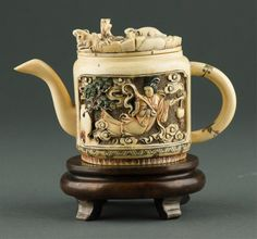 Fine Chinese ivory carved teapot, of cylindrical form, carving with panels of chicken family and Shang Er figure. Top lid with detailed Fu mouse carvings. On custom wood stand.