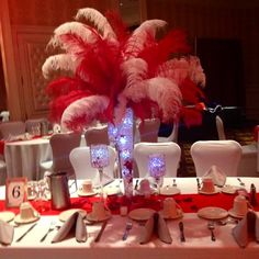 Clear pilsner vase filled with clear jelly balls, red gems and LED lights topped with red and white ostrich feathers and surrounded by trio of pedestals filled with clear jelly balls, red gems and LED lights. Doristhefloristt.com